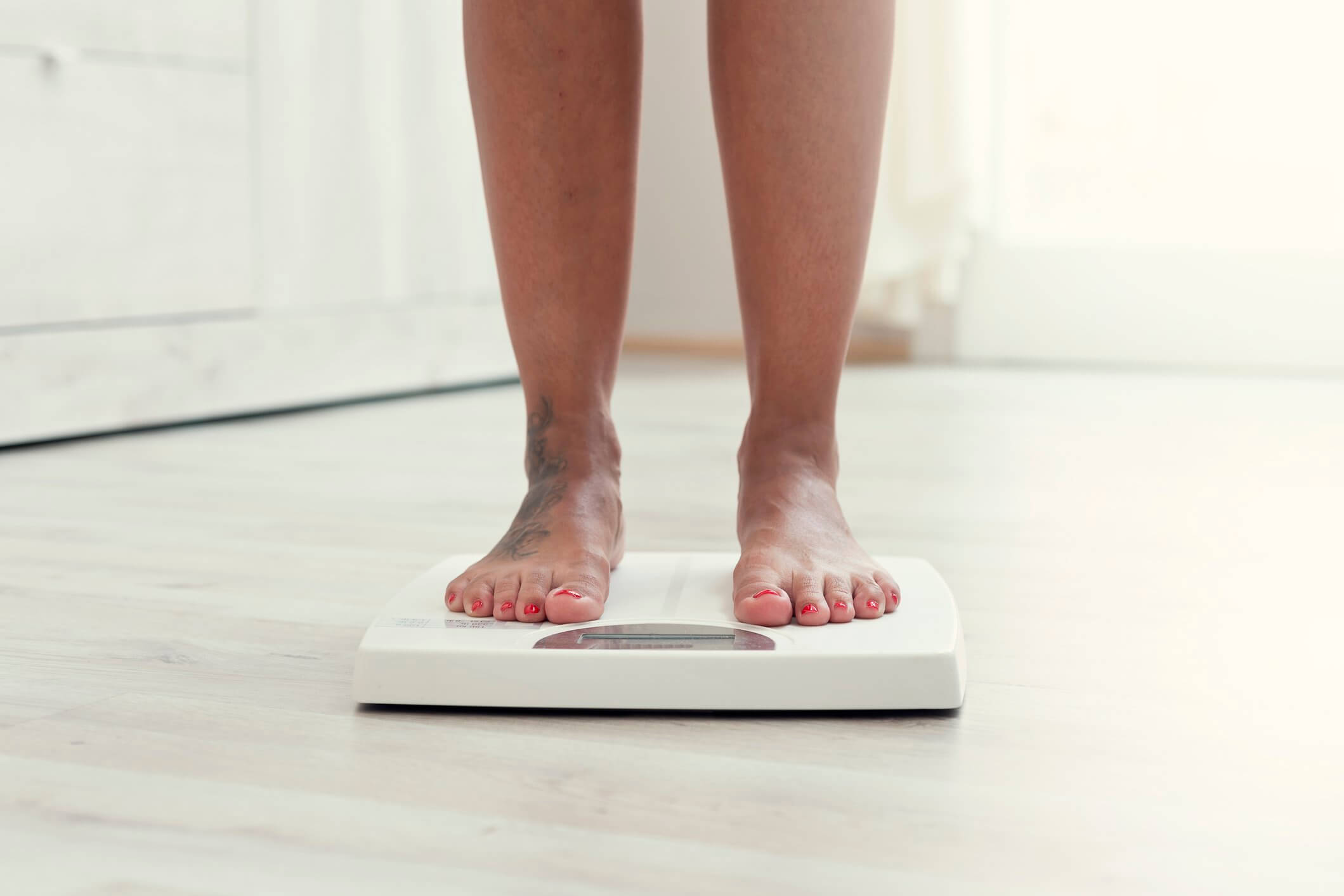 crop image woman standing in weighing scale