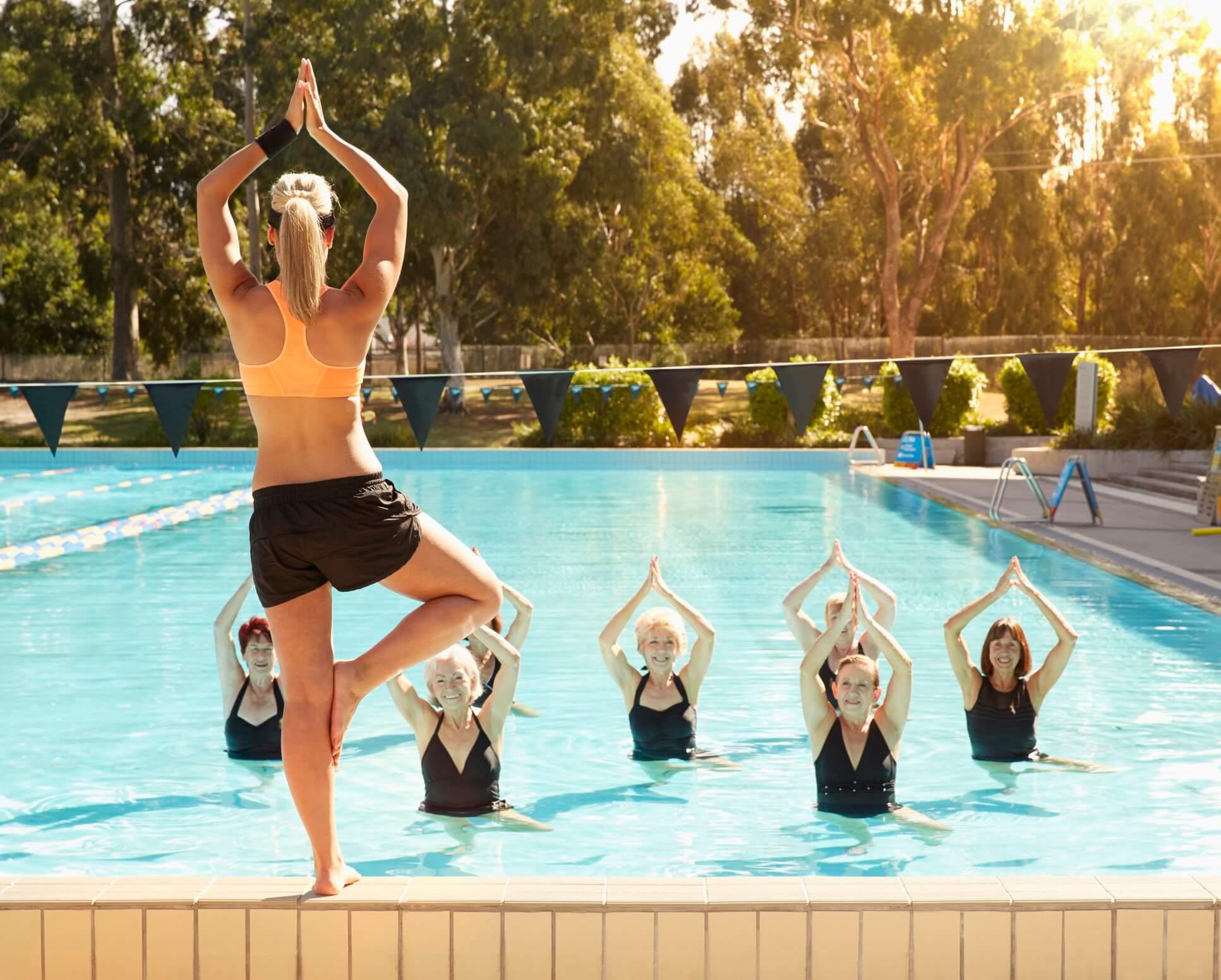 group of women doing yoga in swimming pool