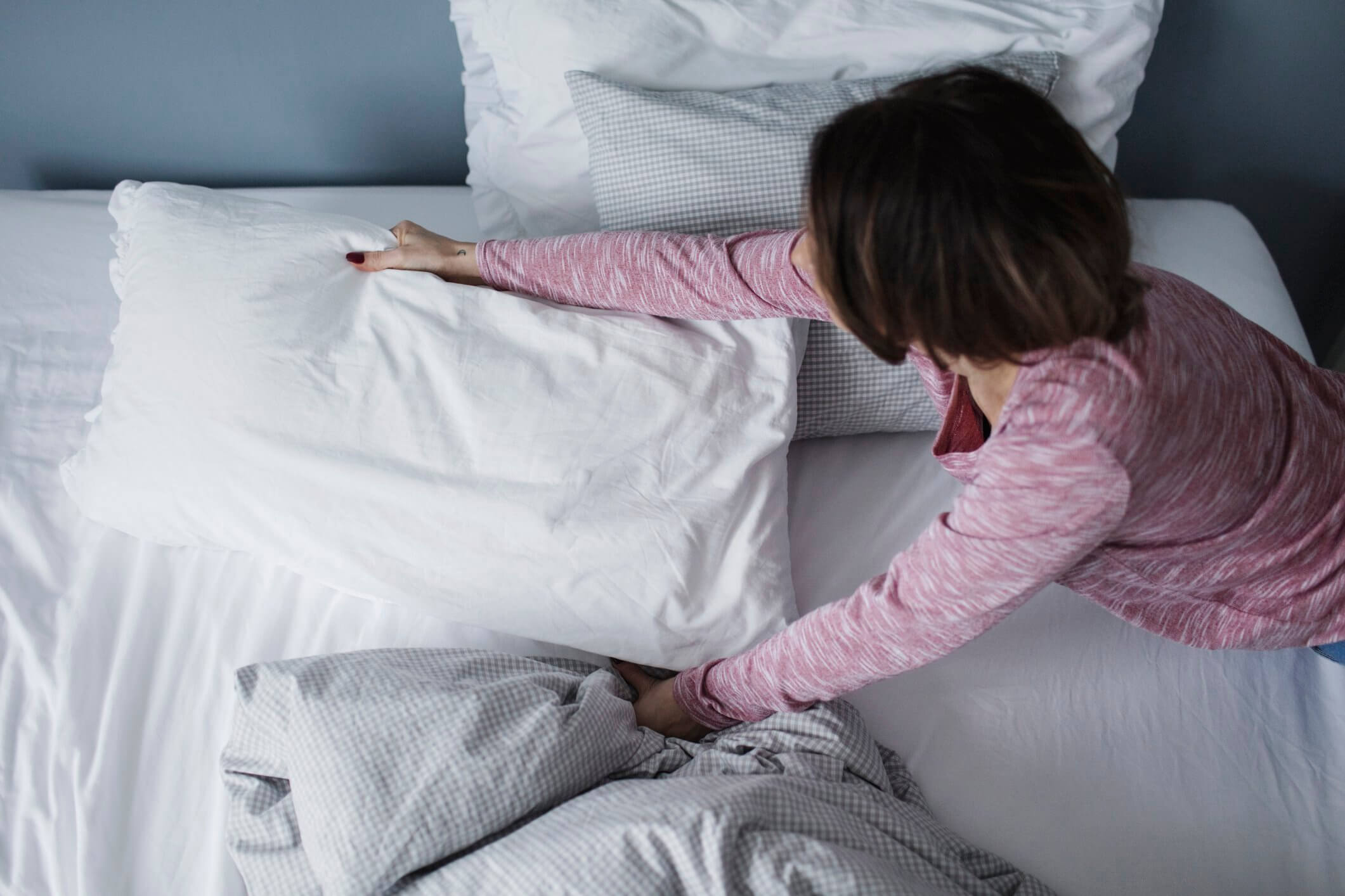 woman fixing bed