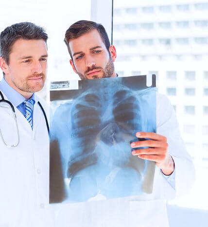 two doctors examining x-ray film